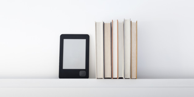Electronic book reader next to traditional books